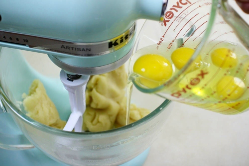Adding eggs one at a time to pate a choux dough (2)