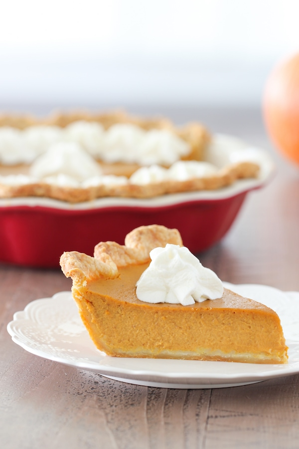 A slice of smooth and tender pumpkin pie with whipped cream and a deep dish pie plate in the background