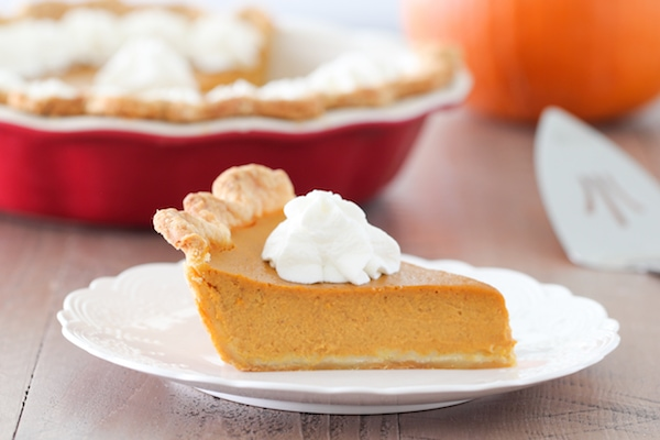 A slice of smooth and creamy pumpkin pie with whipped cream