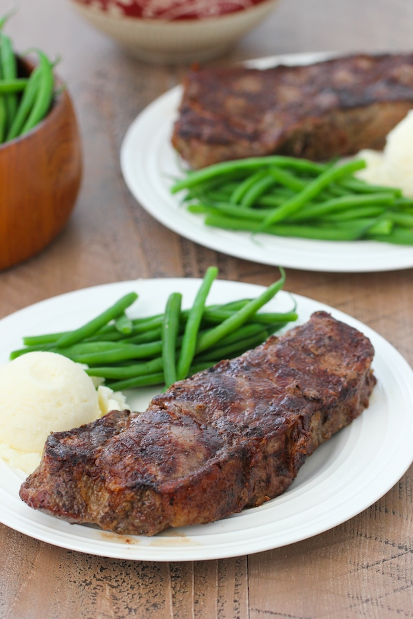 Perfectly grilled steak with grill marks on a plate with mashed potatoes and green beans