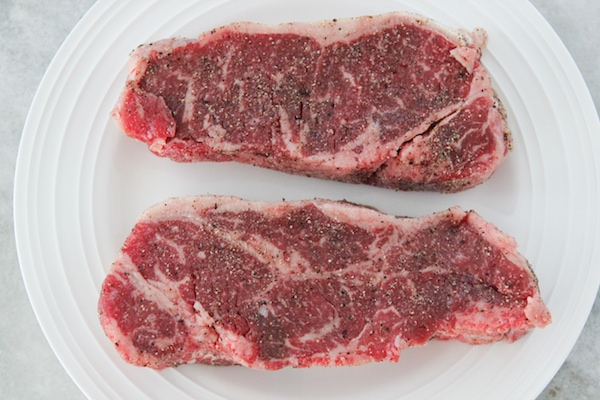 Seasoned steaks on a plate, salt and coarsely ground black pepper