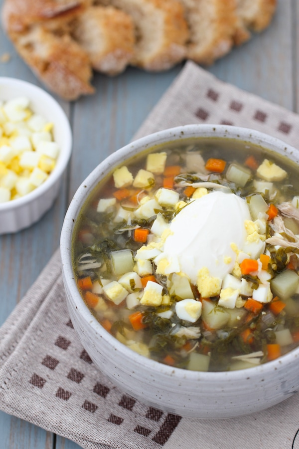 A bowl of Green Borsch; a sorrel soup made with potatoes, onions, carrots and garnished with hard boiled eggs and sour cream.
