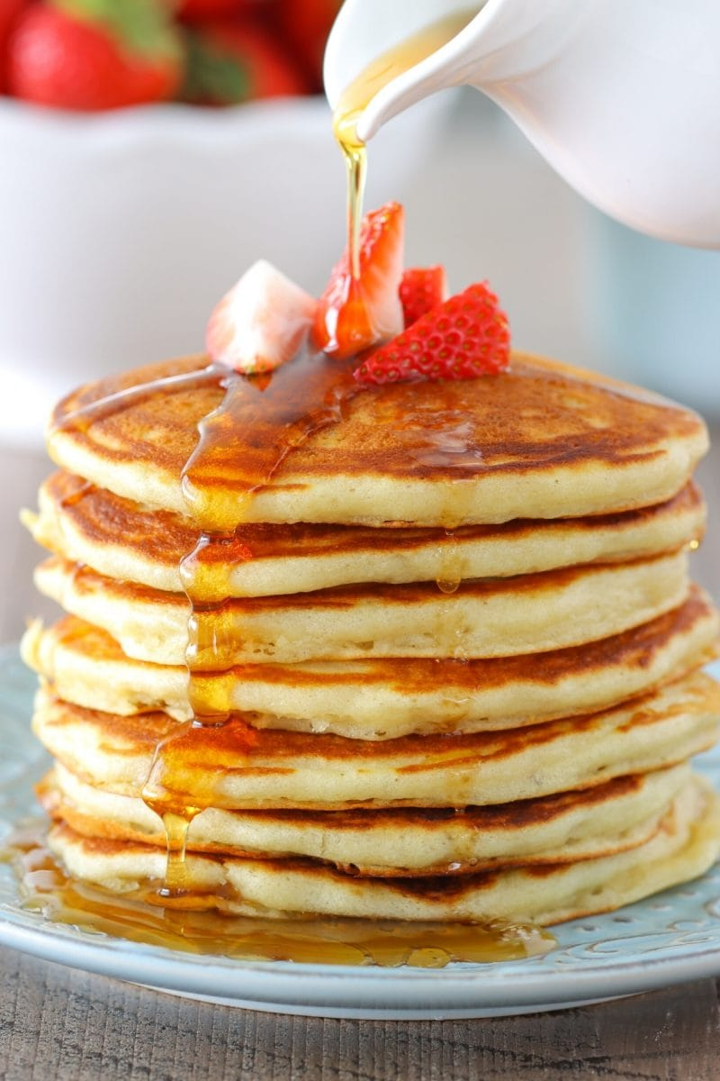 The most tender and fluffy buttermilk pancakes with strawberries and maple syrup.