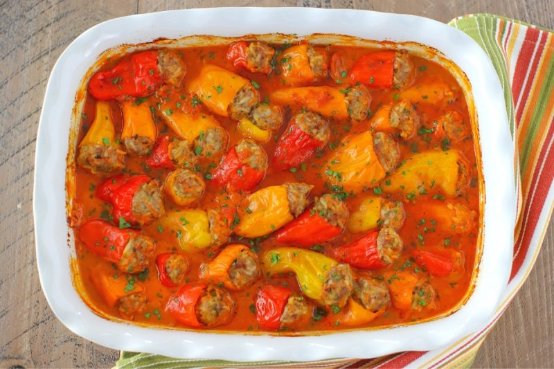 Stuffed mini peppers with tomato sauce in a baking dish