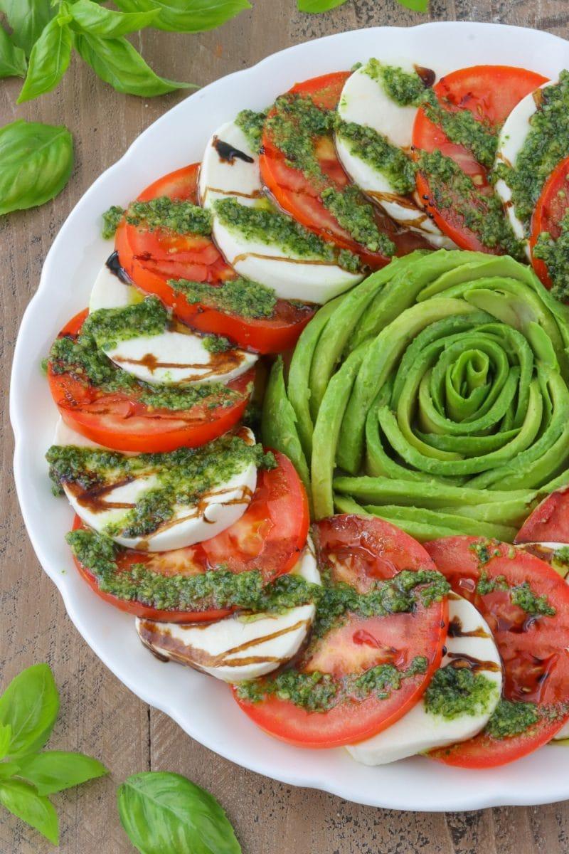 Tomato Caprese salad - tomatoes, avocados, mozzarella cheese, balsamic glaze and pesto sauce.