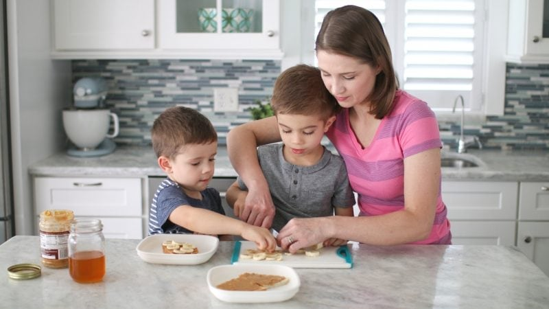 Mom and kids preparing lunch peanut butter and honey sandwiches